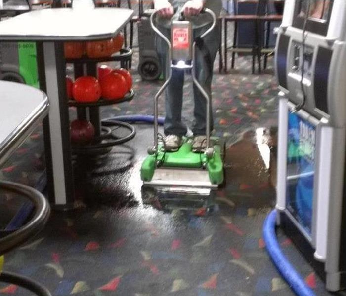 Wet commercial carpet, equipment extracting water from floor, concept commercial water damage