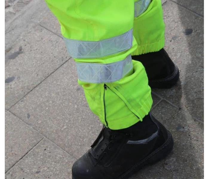 Someone wearing fluorescent green pants and black boots