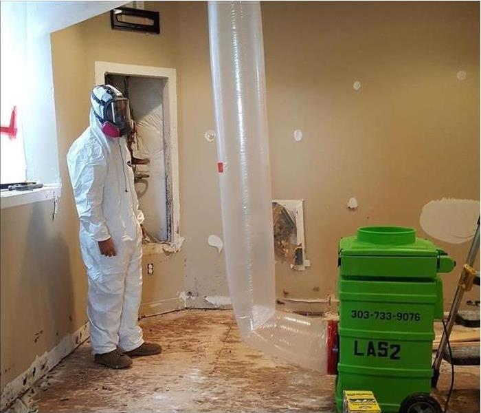 Technician standing in a room, wearing protective equipment, air scrubber in the room. Concept mold remediation